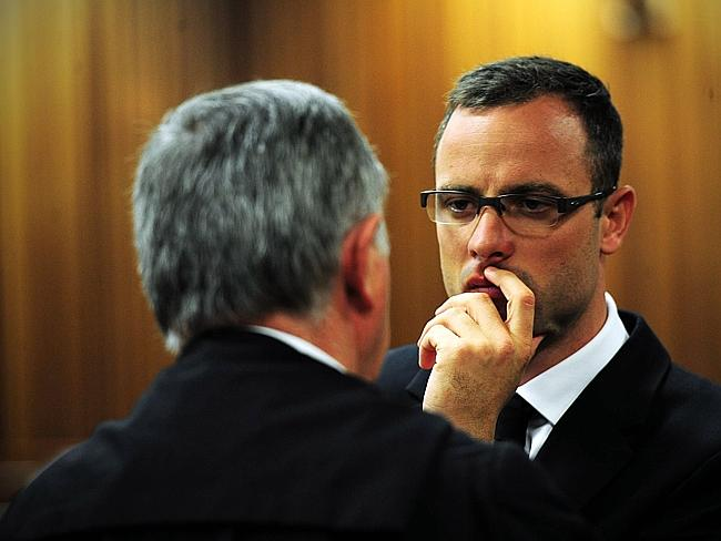 Long trial ... Oscar Pistorius speaks with his lawyer Barry Roux.
