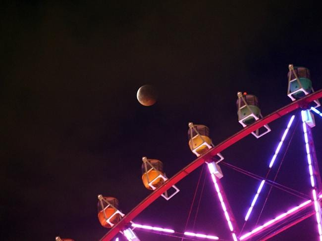 Japan ... the total lunar eclipse is seen behind a ferris wheel in Tokyo. Picture: AFP