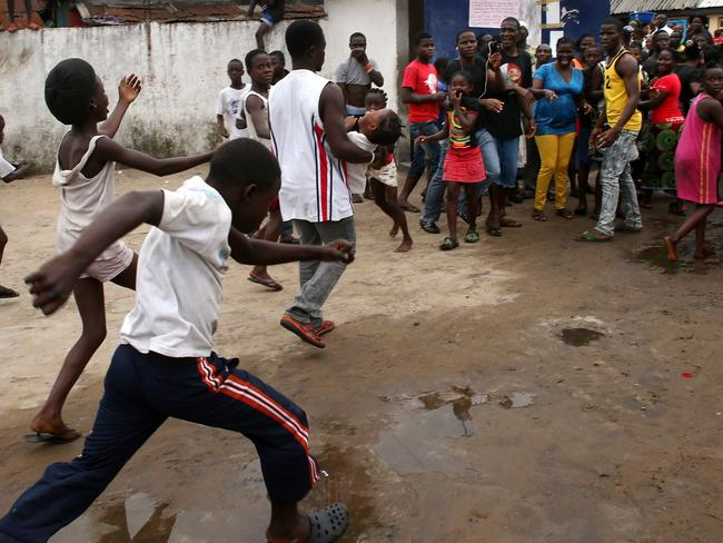 Escape ... a man carries out a girl from an Ebola isolation centre as a mob overruns the facility in the West Point slum in Monrovia, Liberia. Picture: Getty