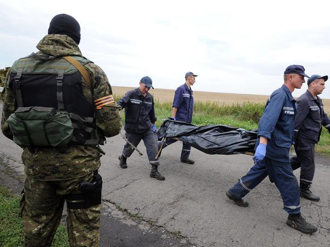 Heavily armed ... Ukrainian rescue workers walk past an armed pro-Russia militant as they carry the body of a victim on a stretcher at the site of the crash of a Malaysia Airlines plane. Picture: Dominique Faget