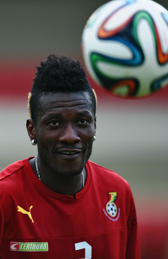 Ghana's forward and captain Asamoah Gyan eyes the ball during a training session at the 2014 World Cup.