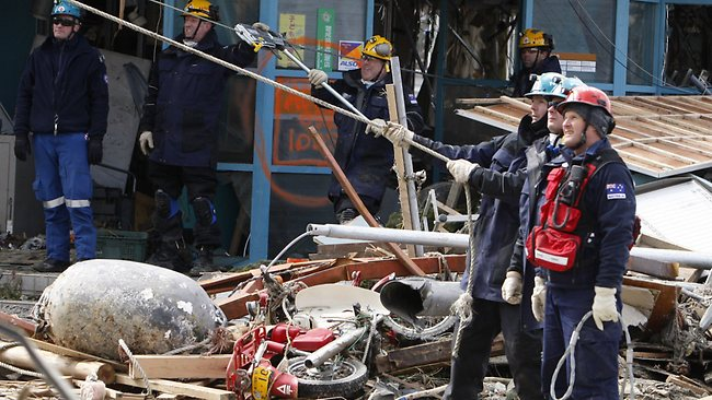 Australian recovery team members dismantle a damaged building in Minamisanriku, Miyagi Prefecture / AP