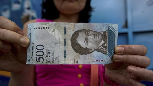 A bank customer shows a new bank note of 500 Bolivars outside a bank in Caracas, Venezuela. In figures released on January 8, Venezuela's opposition-controlled legislature said inflation reached a staggering 2600 per cent last year. Picture: AP/Fernando Llano