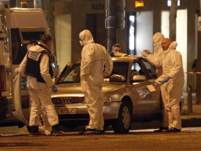 Forensic experts collect evidences from Audi belonging to an attacker who killed a police officer on the Champs Elysees avenue in Paris.