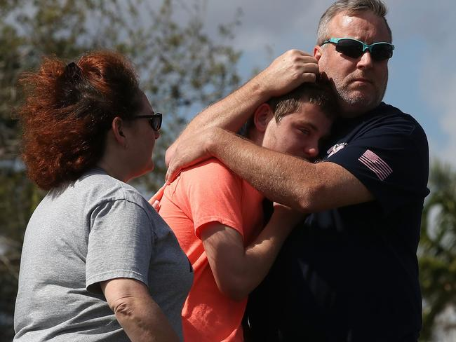 Brian Gruzrnski hugs 14-year-old-son Joshua at Marjory Stoneman Douglas High School where 17 people were killed. Picture: AFP
