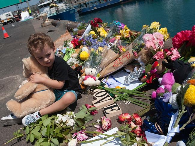 A child sits among the tributes left by mourners at Brennan's Wharf in Port Lincoln, where Damien Little drove his car, containing his two sons, into the water early Monday morning. Picture: Ivon Perrin