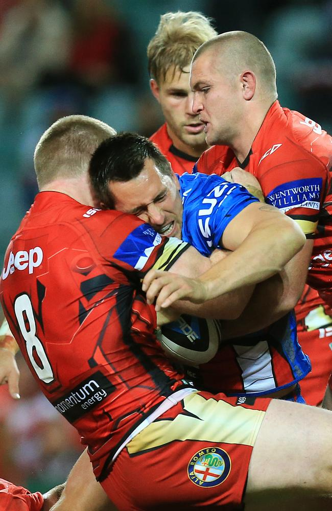 Mitchell Pearce is tackled by the Dragons defence.