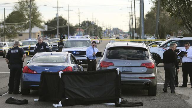 The body of former NFL player Joe McKnight lies between the shooter's vehicle at left and his Audi SUV at right as the Jefferson Parish Sheriff's Office investigates the scene.