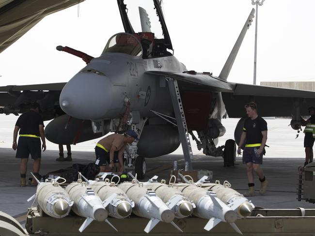 Payload ... RAAF armament technicians load explosive ordnance on an F/A-18F Super Hornet.