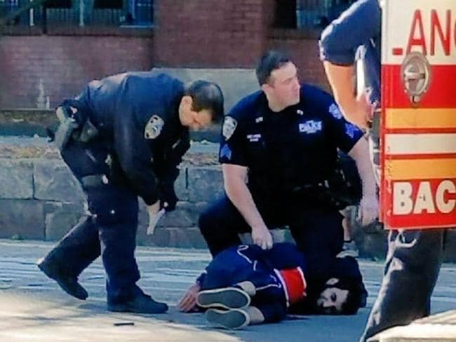 A man is detained by police after mowing down pedestrians on a bike path in Manhattan before ramming a school bus. Source: Twitter/NBC 4 New York