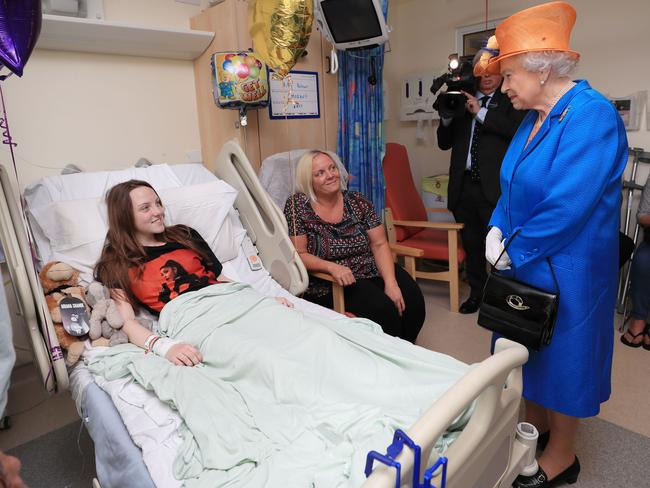 Britain's Queen Elizabeth II speaks to Millie Robson, 15, from Co Durham, who was injured in the Manchester Arena terror attack, and her mother Marie, centre, during a visit to the Royal Manchester Children's Hospital. Picture: AFP / Peter Byrne
