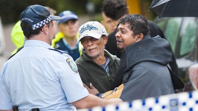 Two men believed to be relatives of the deceased are comforted by police at the site of the drowning in Westmead. Picture: Phillip Rogers