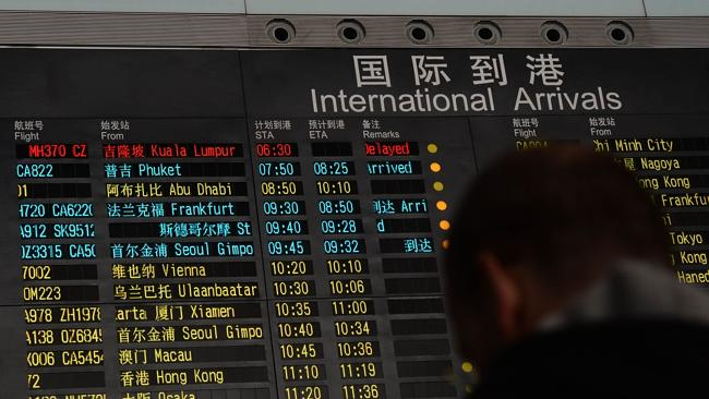 A man stands beside the arrival board showing the flight MH370 (top-red) at the Beijing Airport after news of the Malaysia Airlines Boeing 777-200 plane disappeared.