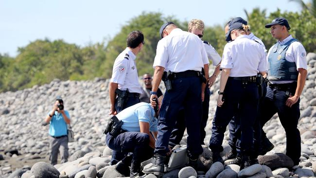 More wreckage ... police officers inspect metallic debris found on a beach in Saint-Denis.