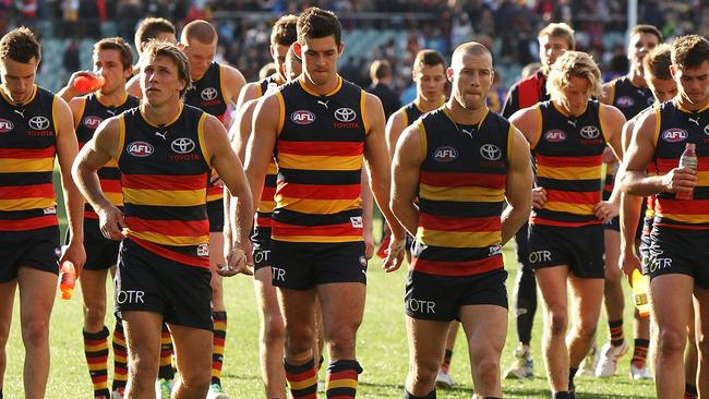Adelaide players trudge off Adelaide Oval after their defeat.