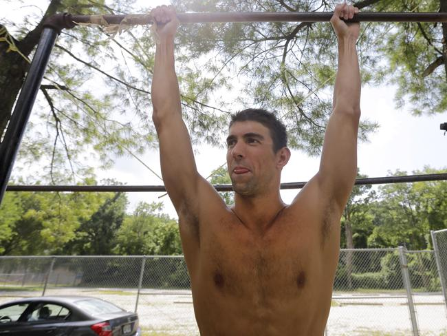 Michael Phelps prepares to do pull-ups.