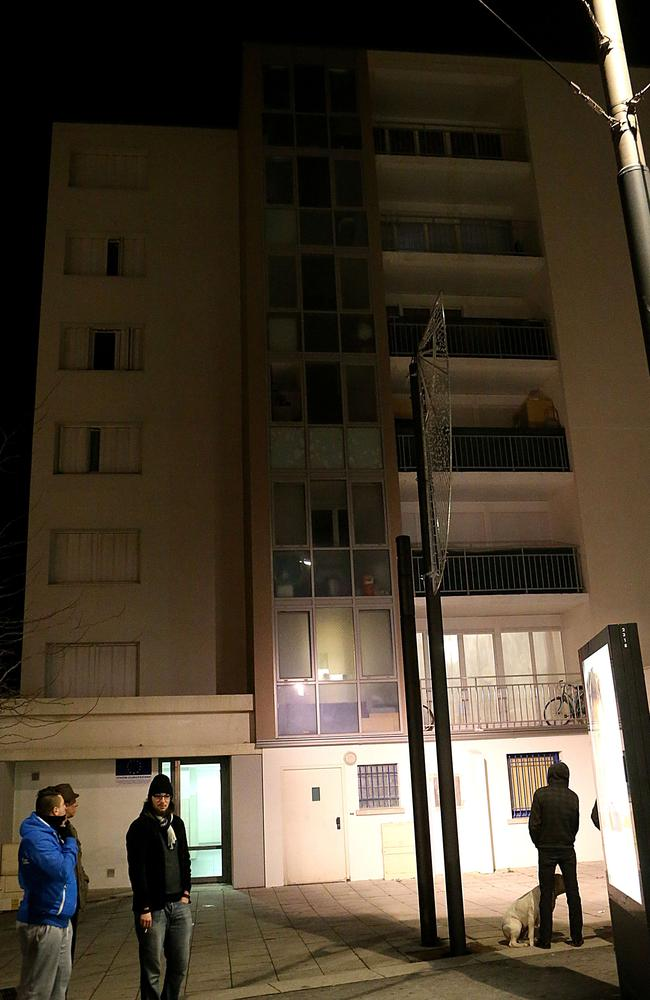 Residents wait outside as French police search the building for evidence relating to the Charlie Hebdo terrorist attack