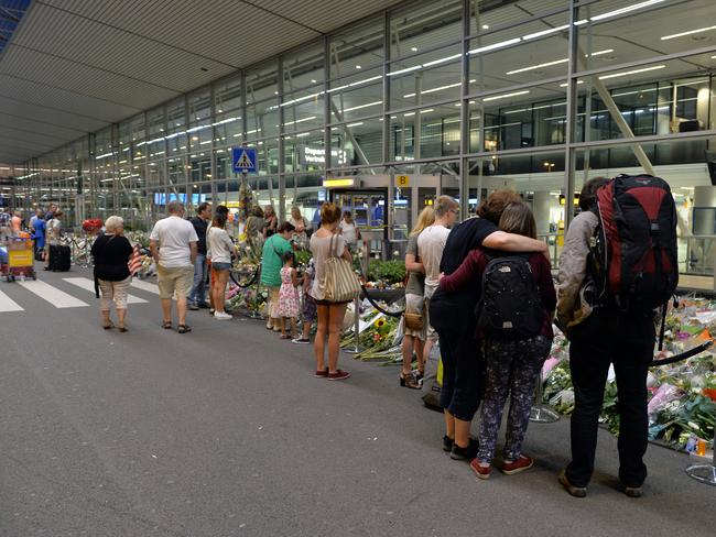 Memorial ... People travelling through Schiphol Airport, Amsterdam, Holland, lay floral tributes to remember the victims of Flight MH17. Picture by Ben Stevens / i-Images