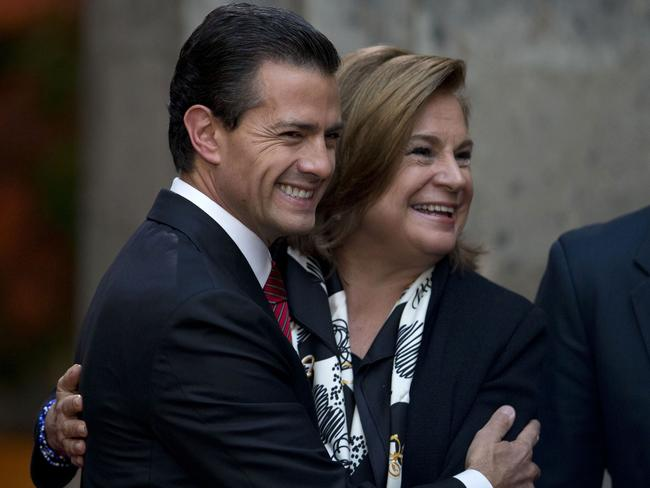 Got him ... Mexican President Enrique Pena Nieto, centre, hugs Attorney General Arely Gomez. Picture: AP