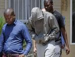 South Africa's Olympic sprinter Oscar Pistorius leaves the Boshkop police station on February 14, 2013 in Pretoria East, to be taken into police custody after allegedly shooting dead his model girlfriend having mistaken her for an intruder at his upscale home. Picture: AFP PHOTO Pic. Afp