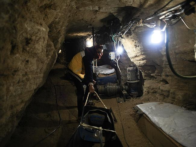 A tunnel worker drags goods through the tunnel between Egypt and Gaza. Picture: Ahmed Dee