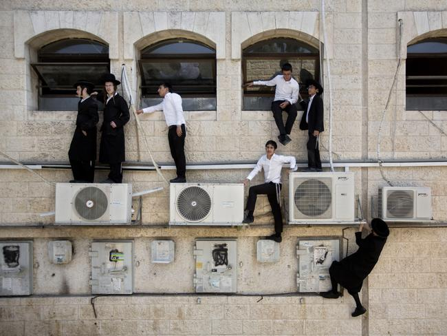 Attack ... Orthodox Jewish boys climb a wall to watch the scene of an attack in Jerusalem. Picture: AP