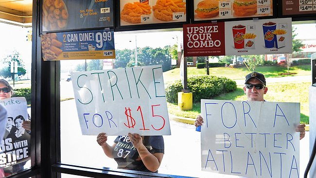 David Atten, right, joins others in demonstrating as he presses a sign to the window of a Church's Chicken during a one-day strike coinciding with strikes at other fast food restaurants across the country, in Atlanta. US fast food workers are demanding $US15 an hour and the right to form a union. Picture: AP