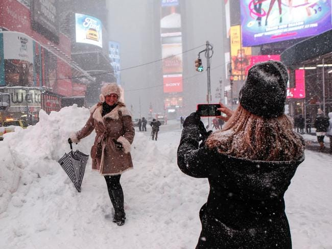 Having fun ... women take photos in Times Square, New York during record-breaking snowfall. Picture: AFP/Kena Betancur