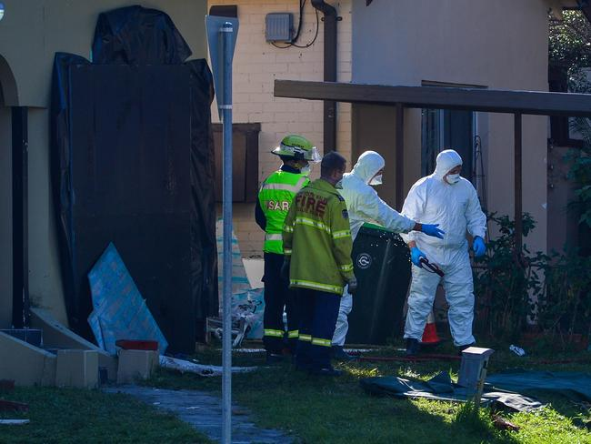Fire and Rescue officers, wearing protective anti-asbestos gear, help NSW Ambulance crews remove a 300kg man from a house. Credit: Diimex