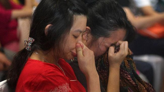 Relatives and next-of-kin of passengers on the AirAsia flight QZ8501 wait prayerfully for the latest news on the search of the missing jetliner at Juanda International Airport in Surabaya, East Java, Indonesia. Pic: AP Photo/Trisnadi Marjan.