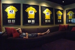 Lance Armstrong takes time out in his trophy room surrounded by Tour de France yellow jerseys. Picture: Twitter