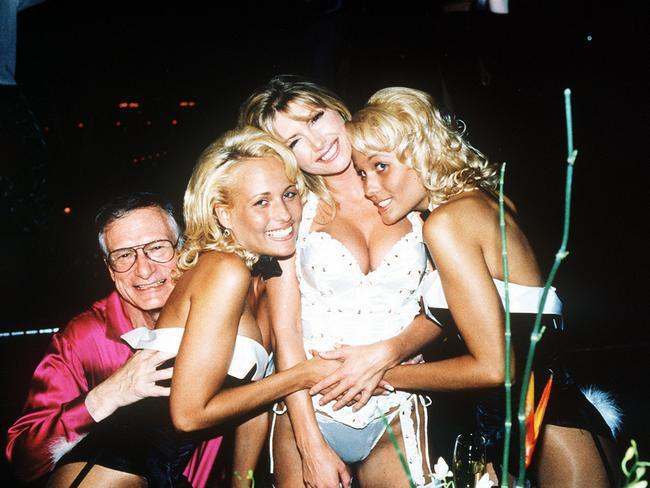 Let's party like it's 1999! Hef with Playboy bunnies, twins Mande Bentley (left) and Sandy Bently (right), with model Brande Roderick (centre) in February 2000.