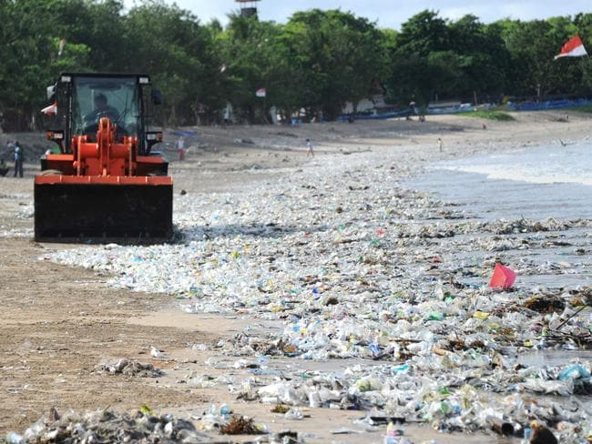 Rubbish collectors are forced to use heavy equipment to clear plastic trash on Kuta. Picture: Sonny Tumbelaka / AFP