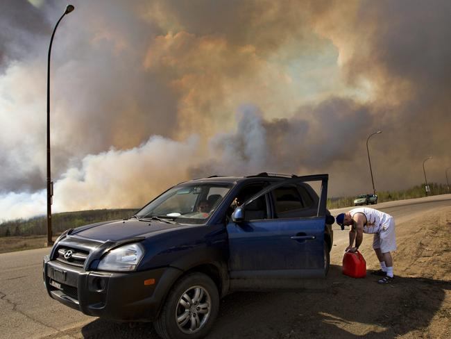 An evacuee puts gas in his car on his way out of Fort McMurray, Alberta, as a wildfire burns in the background. Picture: Jason Franson /The Canadian Press via AP