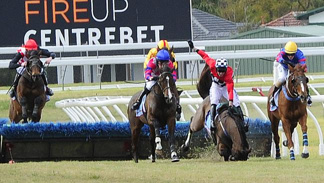 Jockey Paddy Flood and Fantauzzo tumble at the second last hurdle. Both jockey and horse were not injured in the incident. Picture: Mark Brake