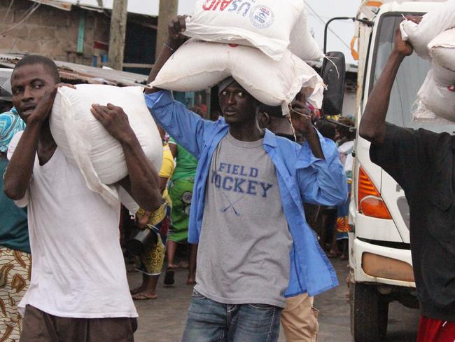 Emergency aid ... men carry food aid in the West Point area of Monrovia, Liberia. Picture: AP