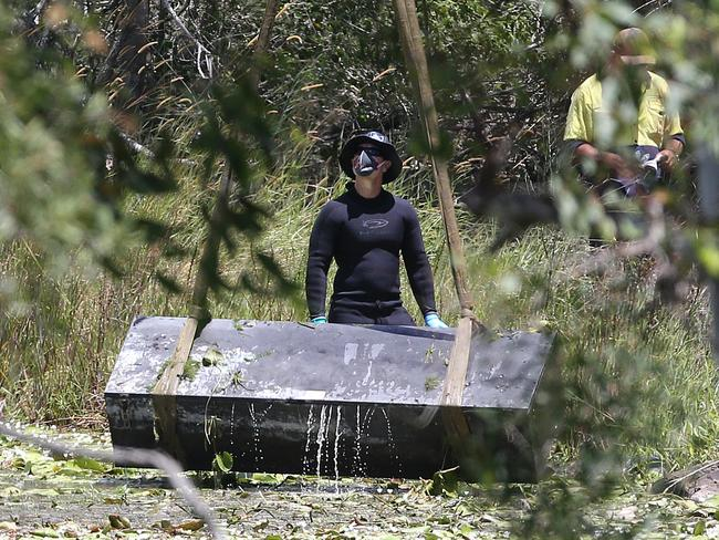 Police retrieve a metal box from a dam near Srubby Creek in Kingston. Picture: Jono Searle