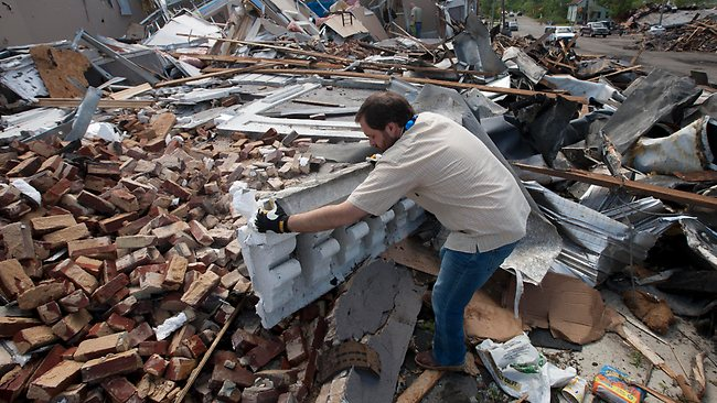 Heath Meherg begins the grim task of cleaning up the wreckage of his business in Cullman, Alabama. Picture: AP