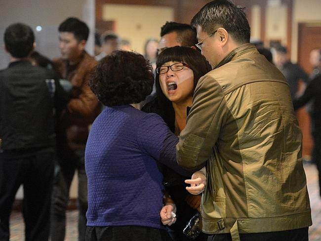 Terrible news ... grieving relatives of passengers on Malaysia Airlines flight MH370 leave a hotel hall at after being told the news that the plane plunged into Indian Ocean.