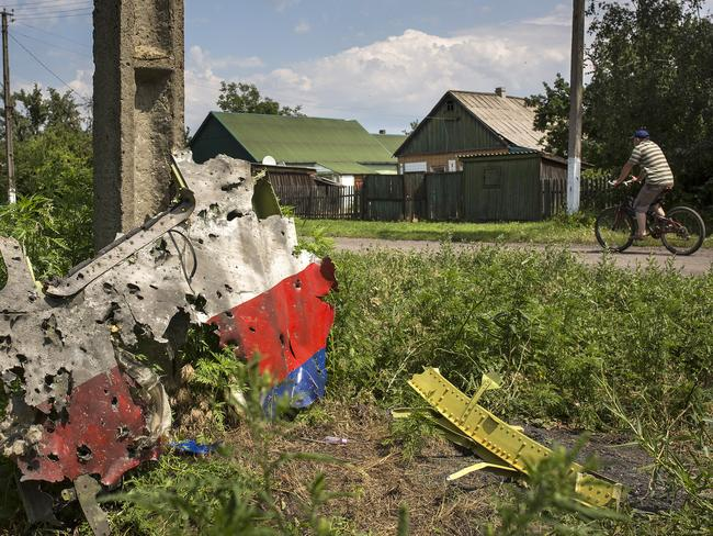A man cycles past a piece of the wreckage of Malaysia Airlines flight MH17 in Petropavlivka, Ukraine. Picture: Rob Stothard/Getty Images