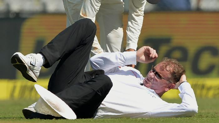 Umpire Paul Reiffel falls on the ground after being hit by a ball on the first day of the fourth Test cricket match between India and England at the Wankhede stadium in Mumbai on December 8, 2016. / AFP PHOTO / Punit PARANJPE / ----IMAGE RESTRICTED TO EDITORIAL USE - STRICTLY NO COMMERCIAL USE----- / GETTYOUT