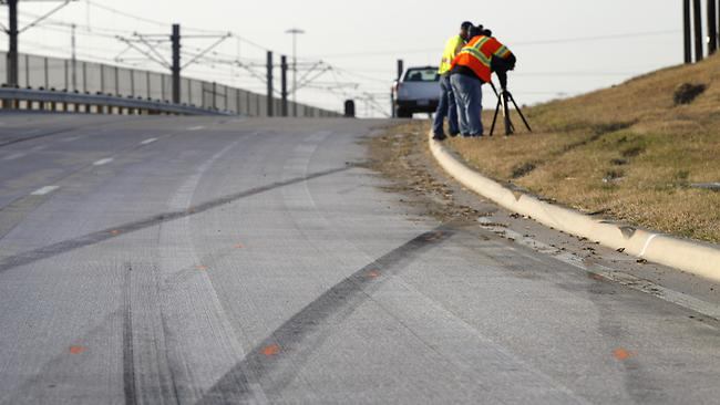 Tire skid marks are seen leaving the road as news cameraman film the area where a single vehicle accident involving Dallas Cowboys player Josh Brent occurred.