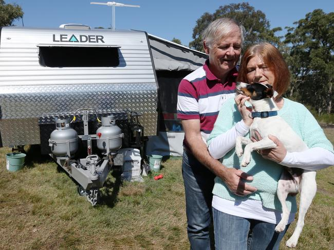 Darren and Elizabeth and Vos (with their dog Banjo) lost their home and now live in a caravan as a result of their losses. Picture: Adam Taylor