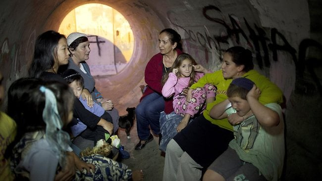 Israelis take cover in a large concrete pipe used as a bomb shelter after a rocket was launched from the Gaza Strip on November 15 in Kiryat Malachi. Picture: Getty