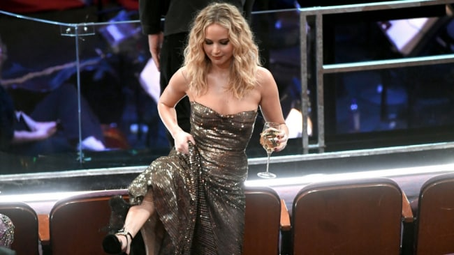 Jennifer, with her wine, jumping over the chairs to get to her seat. Photo: Getty