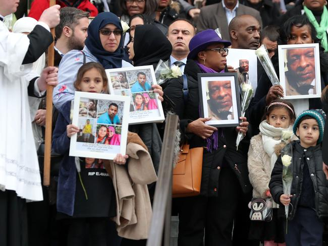 Mourners hold photographs of the loved ones lost in the blaze.