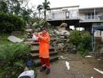 A SES worker takes a picture of one one the few homes to be severely damaged, which lost its roof as a result of the category 4 cyclone Ita , Cooktown , far north QLD