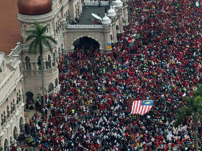Protests ... Malaysians carry a flag during a May Day rally at Independence square in Kuala Lumpur. They are protesting a planned new tax but also took shots over the government's handling of missing flight MH370.