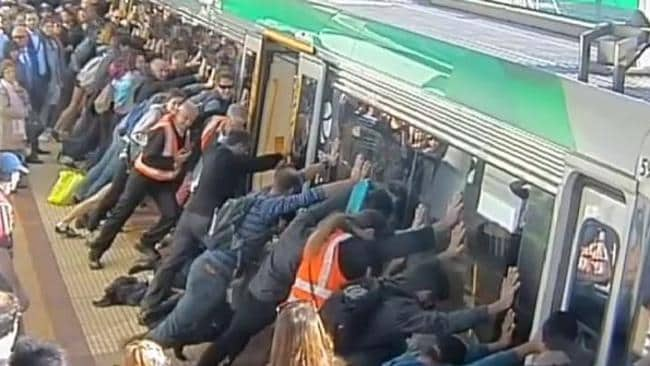 People push a train to free a stuck commuter at Stirling station. Picture: PTA