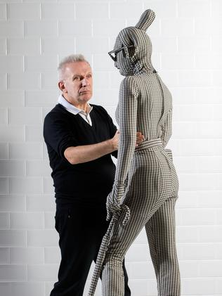 Jean Paul Gaultier makes final preparations to items of couture on a revolving runway as part of his show at London's Barbican Art Gallery. The exhibition is on its way to Melbourne. Picture: Getty